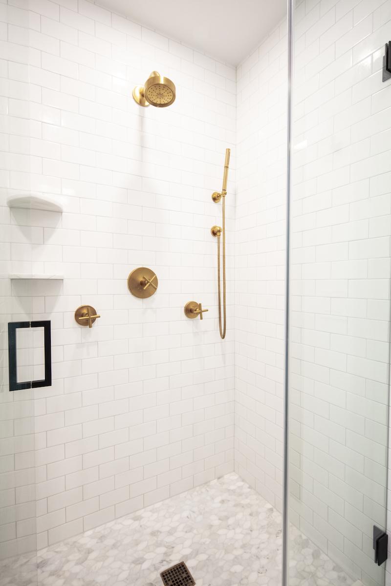 bathroom-shower-gold-hardware-showerhead-tile-floor-subway-tile
