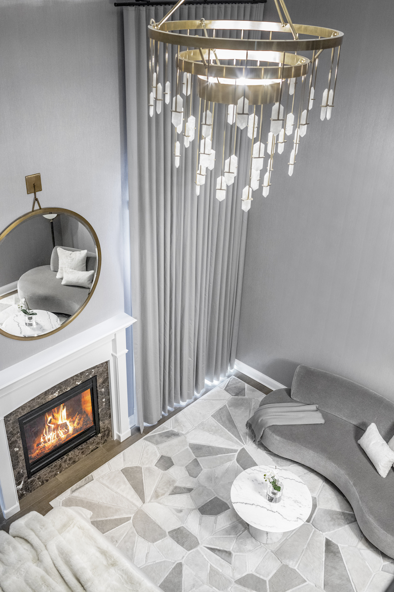 bedroom-chandelier-couch-hanging-round-mirror-over-fireplace
