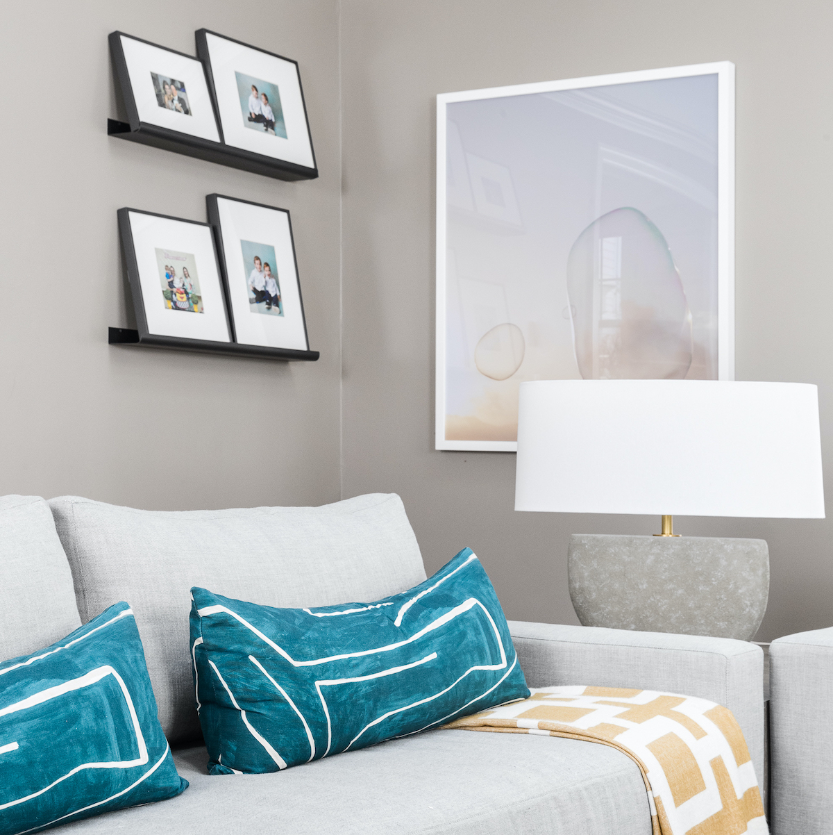 family-room-beige-gray-couch-blue-accent-pillows-yellow-white-blanket